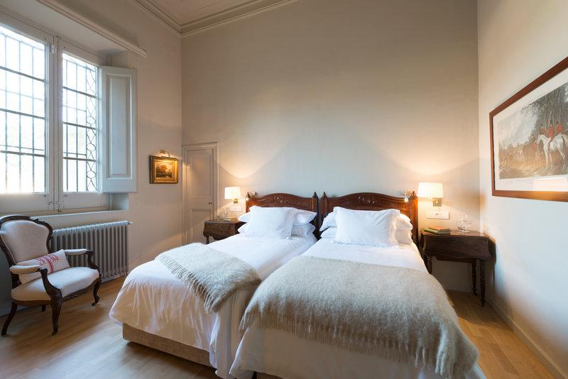 2 single beds with white covers and pillows, a chair, sides tables with lamps and a window in a Barcelona