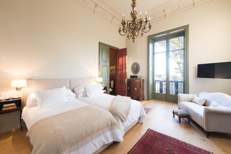 Bedroom with 2 single beds, a couch, a tv in the corner and a private balcony in a Barcelona rental villa