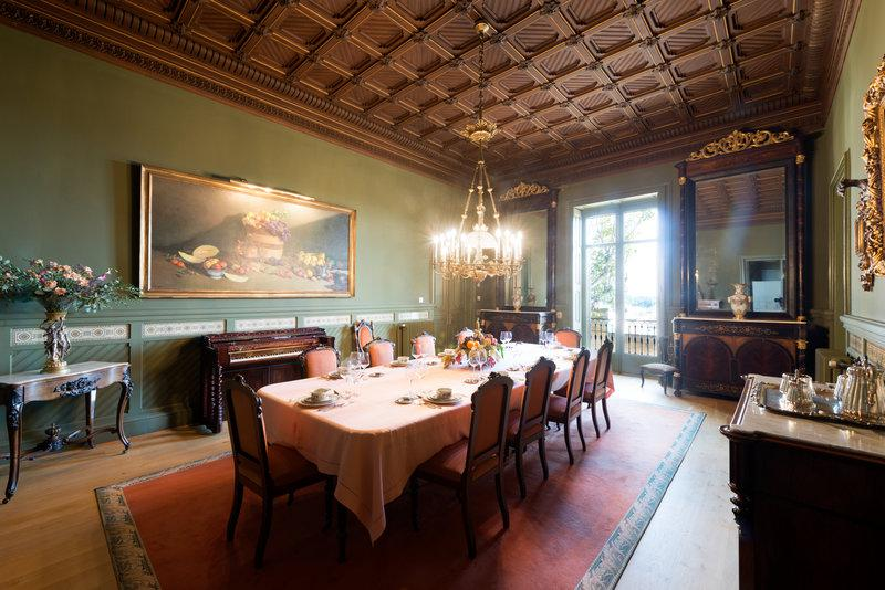 Dining room with piano, paintings, artefacts and a long table for meetings in a Barcelona event villa near to sea